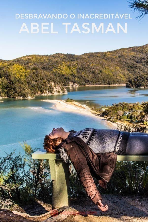 O incrível Parque Nacional Abel Tasman, na Ilha Sul da Nova Zelândia. Um dos menores parques do país, mas repleto de beleza. Cheio de praias, como está da foto, onde pode-se ver uma faixa de areia separando praias de águas azuis. Ao redor, muito verde, com montanhas cheias de árvores. Na foto, uma mulher está deitada embaixo de uma árvore, em um banco de madeira com vista para as praias abaixo. Ela veste roupas de frio.