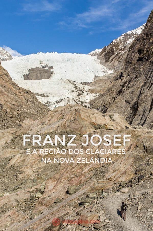 A trilha do glaciar Franz Josef, o mais famoso da Nova Zelândia, fica na Ilha Sul do país. Leva uma hora a ida até o mirante. Um homem caminha pela trilha em meio a rochas cor de terra até o mirante, mas o glaciar está lá no fundo, tímido, mas branco, entre duas montanhas. O céu está azul.