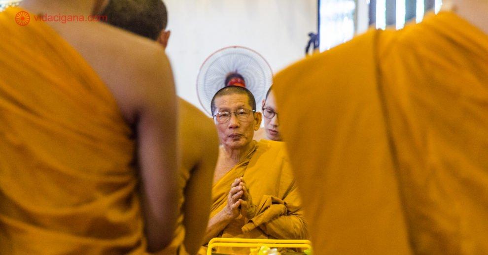 O que fazer em Chiang Mai: um monge budista sentado de frente para a câmera, com outros monges ao redor dele enquadrando a foto.
