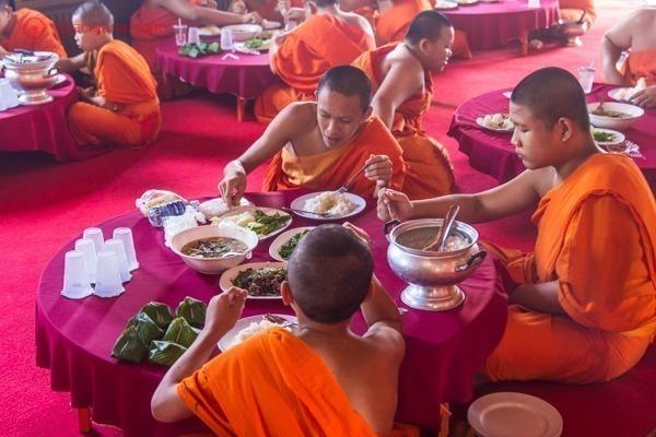 Monges budistas fazendo sua única refeição diária dentro de um templo