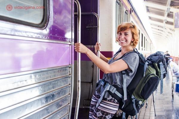Um mulher ruiva em pé na porta de um trem na Tailândia