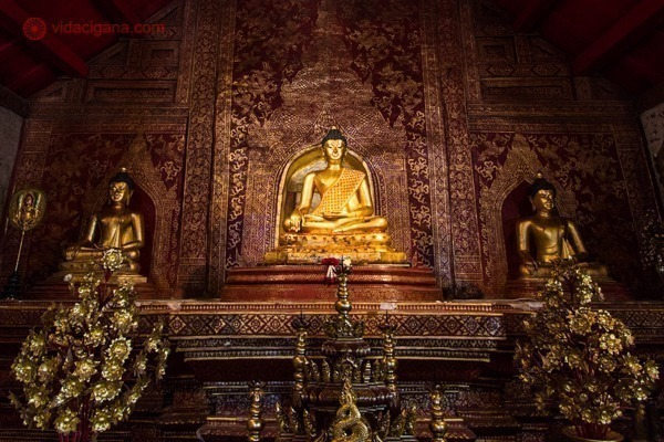 Uma imagem de Buda dourada dentro de um templo bem escuro, com paredes vermelhas