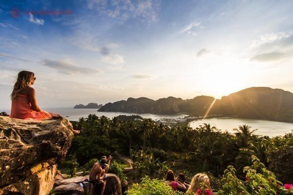 O mirante de Ko Phi Phi Don durante o pôr do sol, com várias pessoas em seu topo observando o sol
