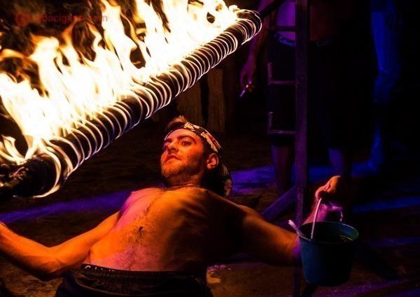 Um homem passando por baixo de uma corda cheia de fogo