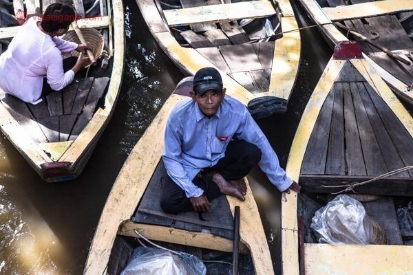 trabalhadores sobre os barcos usados nos passeios pelo delta do mekong