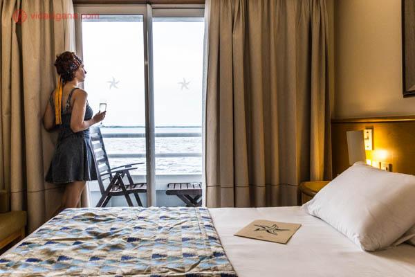 quarto de hotel nacio de cruzeiro da iberostar com cama de casal king size com cobertor azul janela com varanda com vista para o rio solimões e cortina com luz amarela mulher parada com vestido azul tomando prosecco na janela