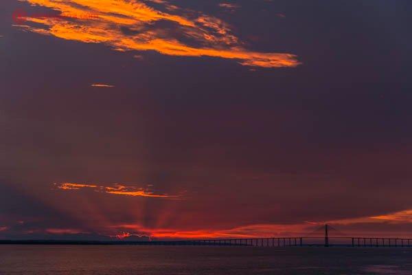 pôr do sol em manaus no rio negro com o céu roxo e rosa com ponte estaiada ao fundo e nuvens laranjas