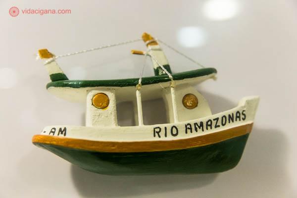 barco de brinquedo de madeira colado na parede branca escrito rio amazonas