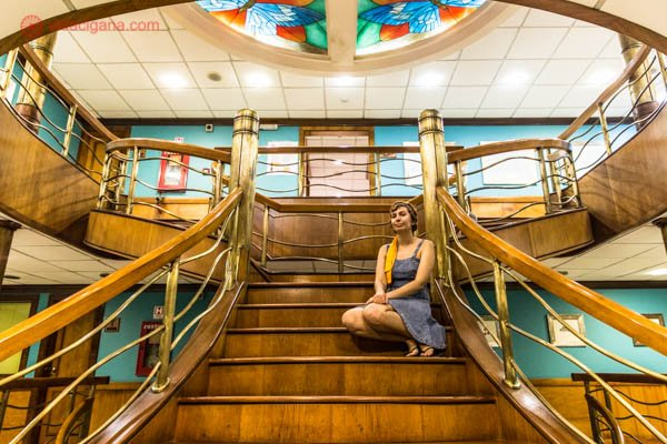 escadaria de navio de cruzeiro da iberostar com mulher sentada usando vestido azul com vitrais no teto coloridos e madeira e parede azul
