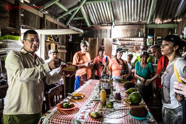 grupo de turistas em uma casa de madeira no amazonas com frutas típicas da região