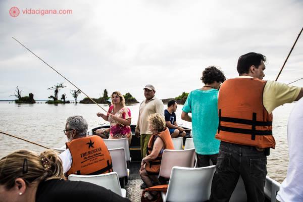 grupo de turistas pescando na beira do rio solimões na selva amazônica vestindo colete salva vidas laranja