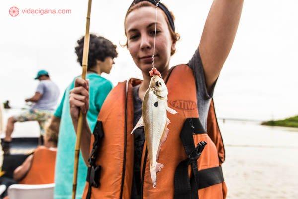 mulher ruiva segurando peixe prata com anzol e vara usando colete salva vidas laranja