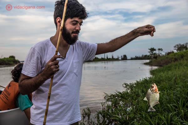 homem moreno de barba pescando um peixe piranha laranja e prata usando camisa branca no rio solimões na selva amazônica