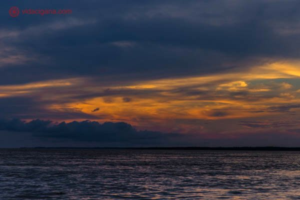 pôr do sol no rio solimões na floresta amazônica com céu azul e laranja com nuvens