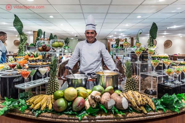 chefe de cozinha vestindo roupa de cozinheiro branca com várias frutas como abacaxi banana e outros frutos panelas com comidas