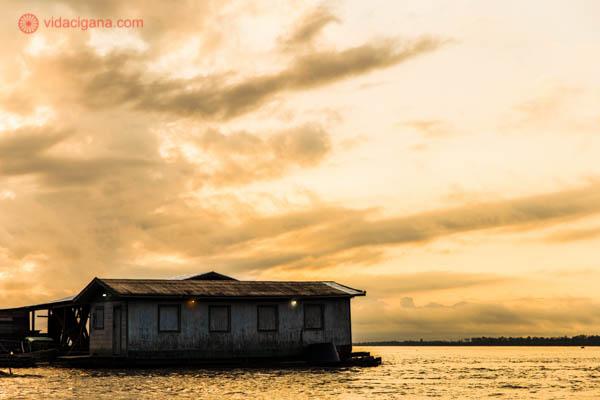nascer do sol no rio solimões dentro da floresta amazônica com o céu laranja cheio de nuvens e uma casa branca flutuando nas águas