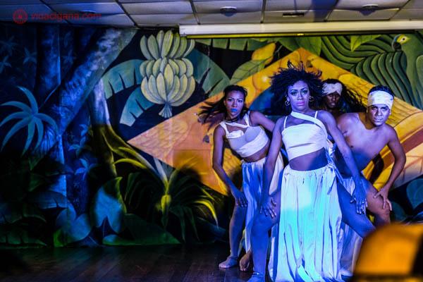 grupo brasileirp dançando em teatro com luz especial azul e fundo com a bandeira do brasil mulheres negras e mulatas vestindo branco