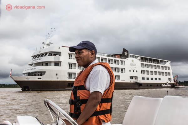 homem negro dirigindo lancha usando colete salva vidas laranja e ao fundo um navio de cruzeiro da iberostar no rio solimões branco com o céu nublado e cinza