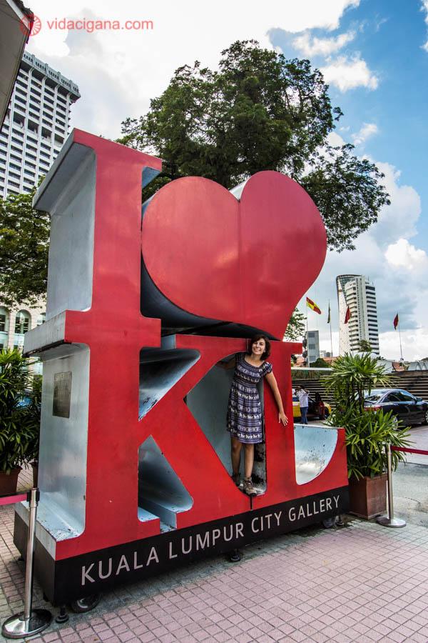 mulher morena posando em frente ao monumento em kuala lumpur, na Malásia, onde está escrito I heart (símbolo de coração) KL, ou seja, Eu amo Kuala Lumpur. A mulher veste vestido com estampa típica do sudeste asiático, com cores azuis, o monumento é na cor vermelha. Atrás pode-se ver árvores verdes, céu azuis e prédios altos.