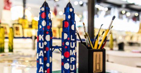 miniatura de brinquedo e feito de papelão das torres petronas de kuala lumpur na Malásia. As torres de brinquedo são azuis com bolinhas em azul claro, vermelho e branco e com os nomes Kuala Lumpur escritos em cada uma das torres. Atrás das torres tem um ponta lápis cheio de pincéis.