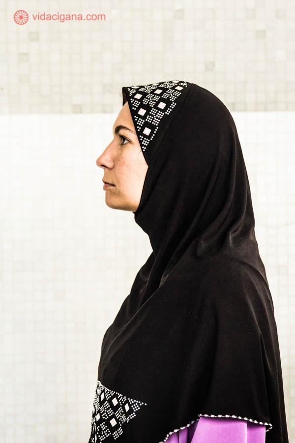 mulher branca usando o hijab, o véu islâmico na cor preta, com bordados dourados no topo do cabeça. A vestimenta usada por baixo é lilás. A foto foi tirada de perfil.