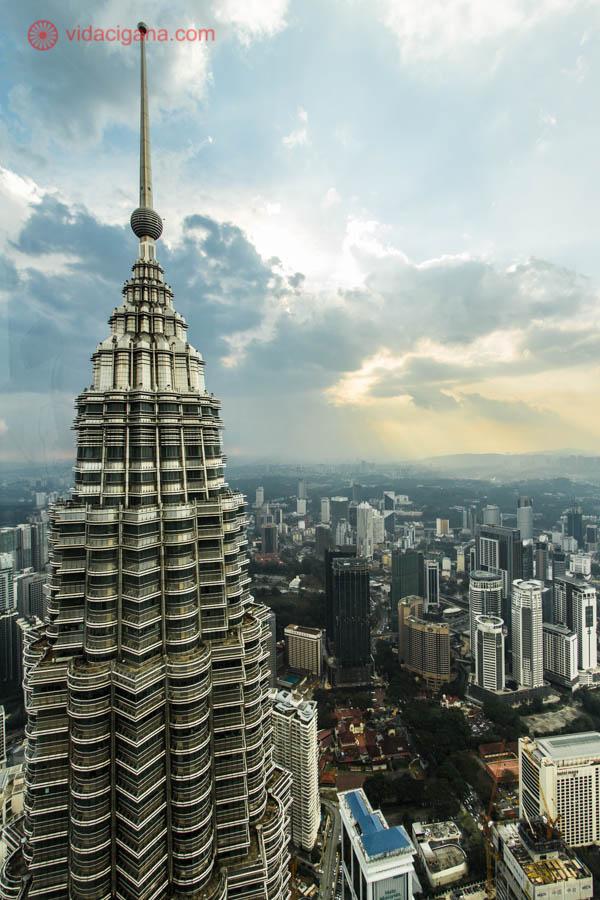 Uma torre Petronas vista do alto de outra torre petronas, O céu está nublado e lá embaixo é possível ver toda a cidade de Kuala Lumpur, na Malásia, cheia de prédios altos. As torres petronas tem um formato de ogiva, e em seu topo, uma antena pontiaguda se encontra.