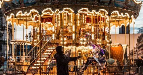 Carrossel dourado e clássico em Paris, com morador de rua fazendo bolhas de sabão na frente dele. O homem veste um casaco preto com capuz. O carrossel é no estilo antigo, com cavalos e luzes com lâmpadas bolinhas.