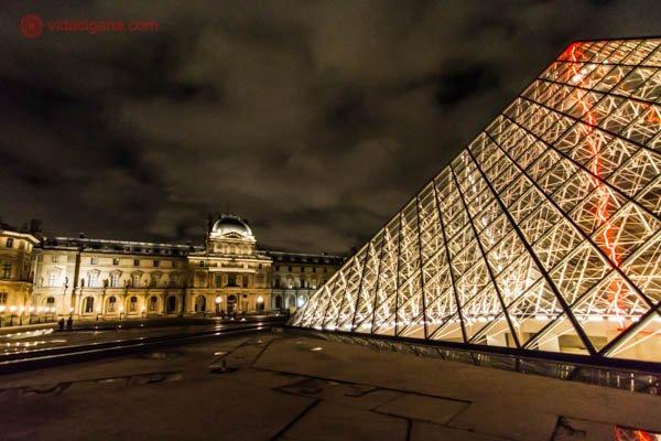 O Museu do Louvre de fora com sua famosa pirâmide de vidro feita na década de 90 por um arquiteto chinês. No interior da pirâmide é possível ver um raio laser na cor vermelha. O Palácio do Louvre, que abriga o museu, está no fundo da foto. O céu está bastante nublado, onde é possível ver as nuvens passando. A foto foi tirada a noite, com os prédios todos iluminados.