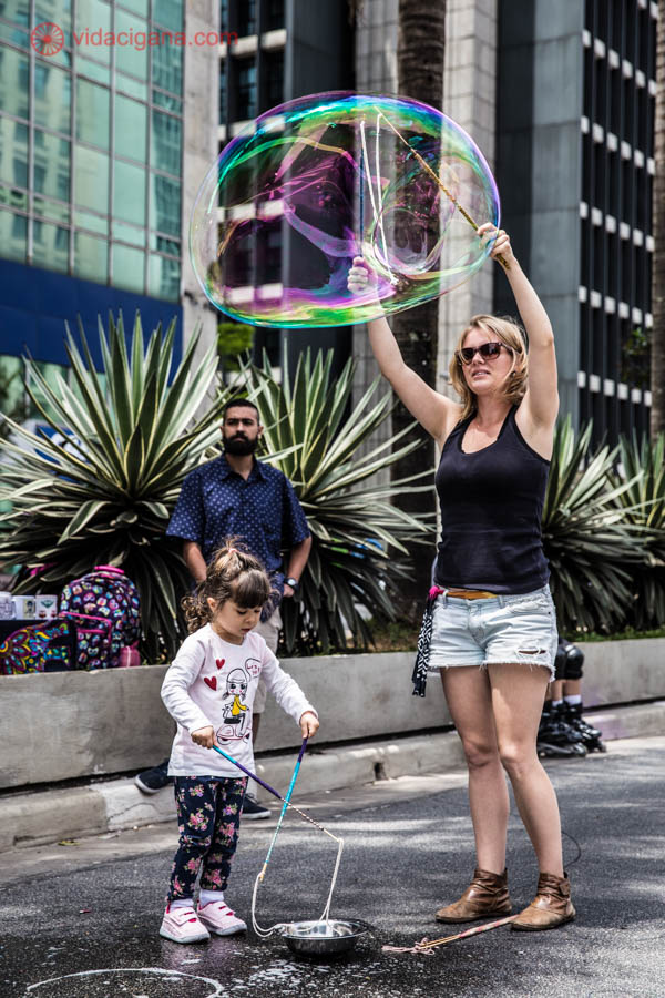 Mulher loira faz bolhas de sabão gigantes na Avenida Paulista, em São Paulo. Uma menina pequena também brinca com as bolhas na rua. A mulher veste camisa preta e short jeans e a menina, camisa de manga comprida e calça florida.