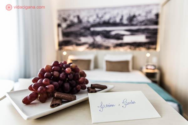 """Um cartão branco escrito """"Larissa e Carlos"""" do lado de uma travessa com uvas vermelhas e pedaços de chocolate. No fundo da foto está uma cama de casal com lençois brancos, travesseiros marrons e cobertor azul. Na cabeceira, uma foto de São Paulo em preto e branco."""
