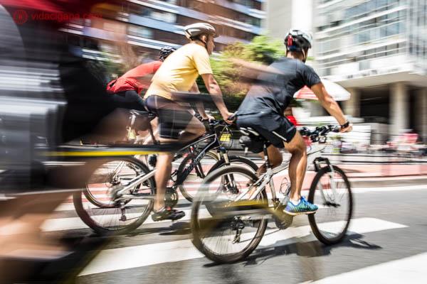 dois homens andando de bicicleta na avenida paulista em são paulo. Os dois estão usando capacetes. A foto é um panning das bicicletas em movimento e tudo ao redor borrado.