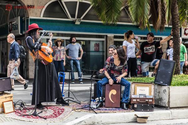 Duas mulheres se apresentando na rua, uma de saia preta e tocando um violão e outra sentada na percursão. Ambas são morenas, uma usa chapéu vermelho e a outra, óculos escuros. Muitas pessoas as olham tocar.