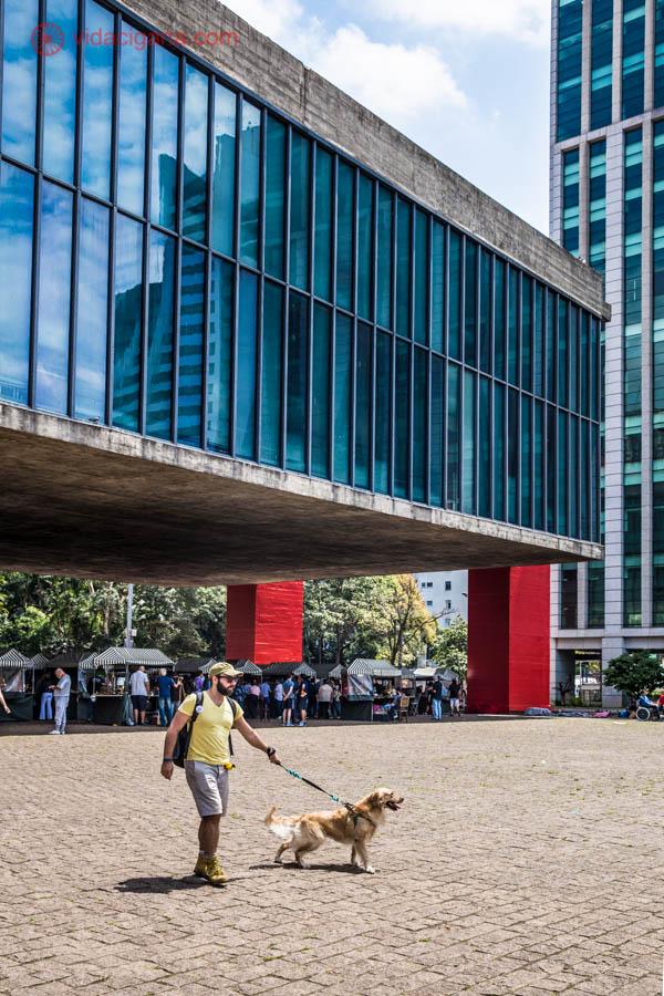 O MASP na Avenida Paulista, em São Paulo, com seus pilares vermelhos e suas janelas azuis. Um homem de blusa amarela e usando boné é puxado por seu cachorro, da raça golden retriever.