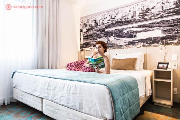 Uma mulher de cabelos ruivos e curtos deitada numa cama de casal. Ela veste um vestido rosa com desenhos de flores vermelhas. Ela está deitada de lado lendo um livro de capa azul. A cama é grande, com lençois brancos, travesseiros marrons e cobertor azul. Atrás da cabeceira fica uma foto de São Paulo em preto e branco.