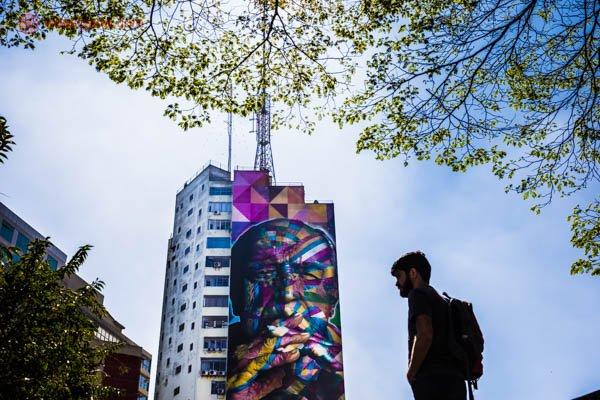 Homem moreno de barba e cabelos pretos carregando uma mochila. Ele está de perfil, na sombra. Ao fundo tem um prédio com um painel colorido do artista brasileiro Kobra. No painel estpa retratado o arquiteto brasileiro Oscar Niemeyer. Copas das árvores emolduram a foto. O céu está azul.