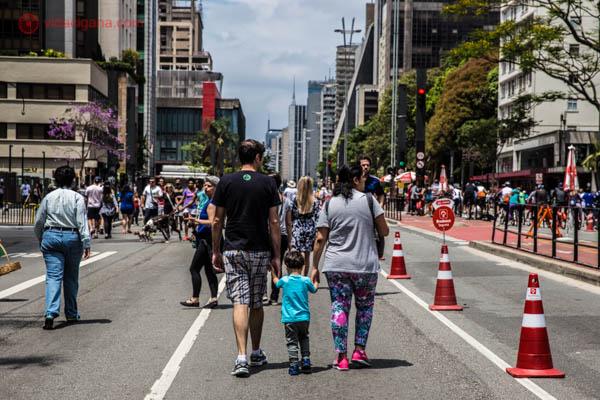Família caminha na Avenida Paulista em São Paulo. Uma mulher e um homem dão a mão a um menino pequeno. Ao fundo, vários prédios podem ser vistos. Na pista tem cones de trânsito também.