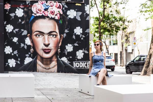 Mulher ruiva de cabelos curtos usando uma bandana amarela e azul e óculos escuros. Ela usa também um vestido jeans azul claro. Está sentada em um cubo branco de pernas cruzadas. A foto foi tirada na frente de um mural de street art na rua Oscar Freire em São Paulo. O mural é da Frida Kahlo e faz parte da loja Iódice.