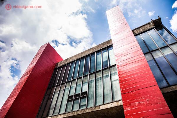 O MASP visto de baixo para cima. Suas colunas são vermelhas e suas janelas são azuis. O céu está azul com nuvens brancas.