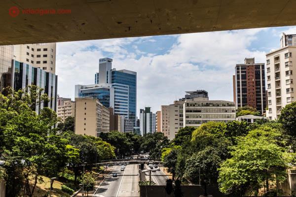 O Mirante 9 de Julho, na Avenida Paulista, em São Paulo. Lá de cima podemos ver a pista embaixo, cercada de árvore e vários prédios ao fundo. O céu está azul, com nuvens brancas. Acima, um viaduto passa por cima.