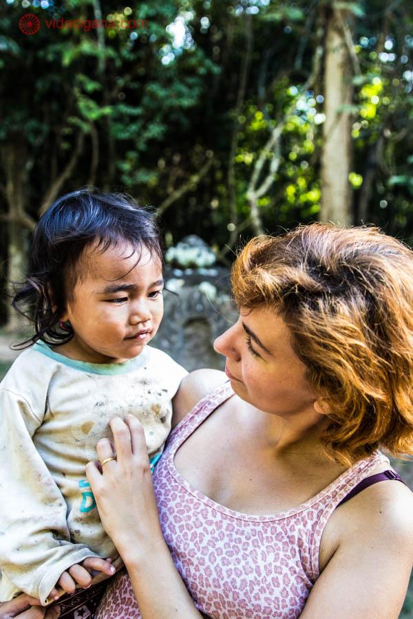 mulher ruiva segurando menina asiática no colo árvores verdes cabelo preto olhos puxados camboja angkor wat sudeste asiático