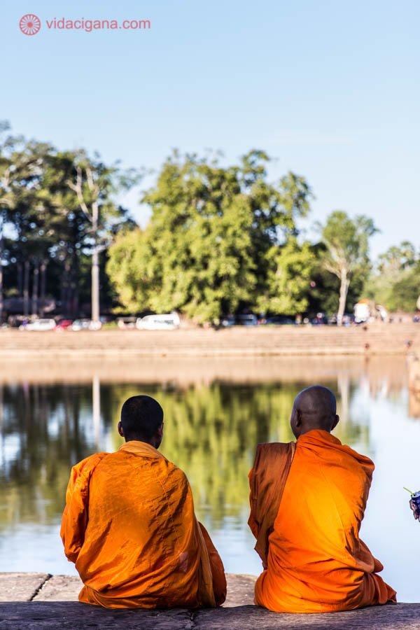 dois monges budistas vestindo roupas típicas laranjas com a cabeça raspada na frente de um lago que reflete céu azul árvores verdes homens sentados conversando