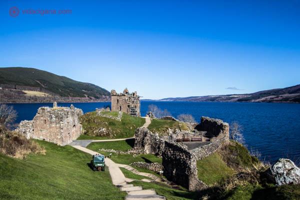 O Castelo de Urquhart, na Escócia, com o Lago Ness, ou Loch Ness, no fundo. O céu está azul sem nenhuma nuvem. O lago possui uma cor azul profunda, lindíssima. Montanhas estão dos dois lados do lago. As ruínas do castelo se encontram em primeiro plano, feito de pedras, muros e torres. Algumas árvores estão secas no local. O castelo fica numa área gramada e verde.