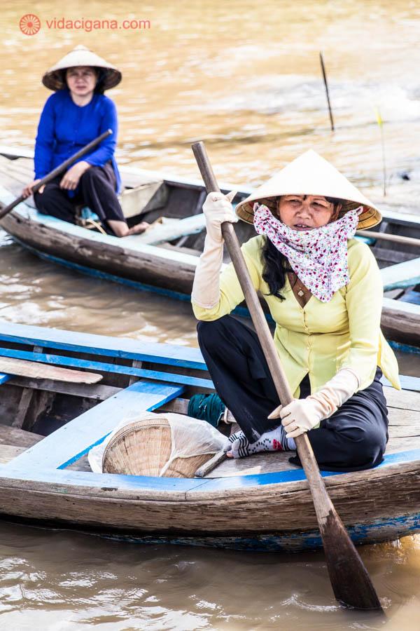 Duas mulheres vietnamitas segurando remos, em cima de barcos típicos. Essas usam o chapéu tradicional do Vietnã, em formato triangular. Elas estão em rios do Delta do Mekong, no Sul do Vietnã.