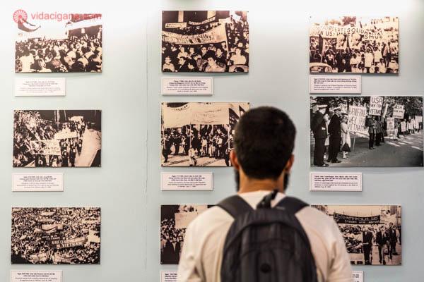 Homem moreno de costas carregando uma mochila observa um mural com várias fotos em preto e branco da Guerra do Vietnã, exibidas no War Remnants Museum, na Cidade de Ho Chi Minh, no Vietnã