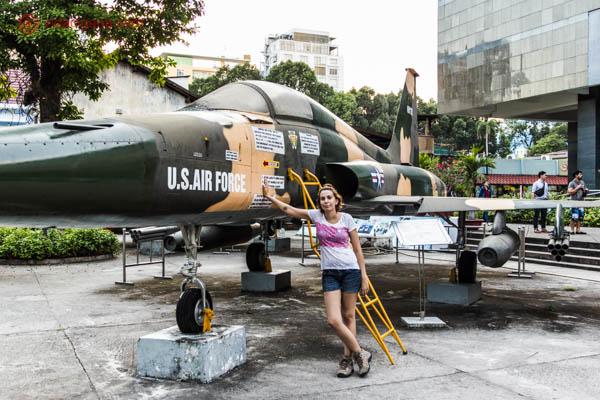 Mulher ruiva com cabelo curto, vestindo uma blusa branca com detalhes rosas, short jeans curto e botas de caminhada, está apoiada em um caça americano, um avião capturando pelos vietnamitas durante a Guerra do Vietnã.