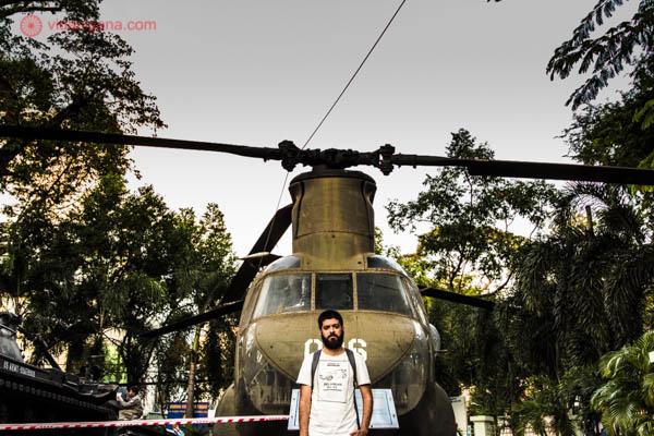 Homem moreno de barba, vestindo uma blusa branca e carregando uma mochila, posa na frente de um helicóptero americano capturado pelos vietnamitas durante a Guerra do Vietnã. Essa foto foi tirada na Cidade de Ho Chi Minh, antiga Saigon, capital do Vietnã do Sul na época. O helicóptero faz parte da coleção de antigos equipamentos de guerra do War Remnants Museum.