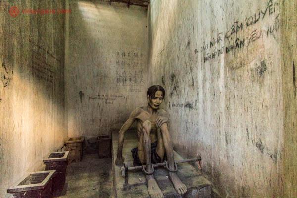 Boneco representando um prisioneiro de guerra vietnamita na Cidade de Ho Chi Minh, no Vietnã. Essa imagem pode ser vista no War Remnants Museum. Nas paredes em volta vemos várias frases em vietnamita. e chinês