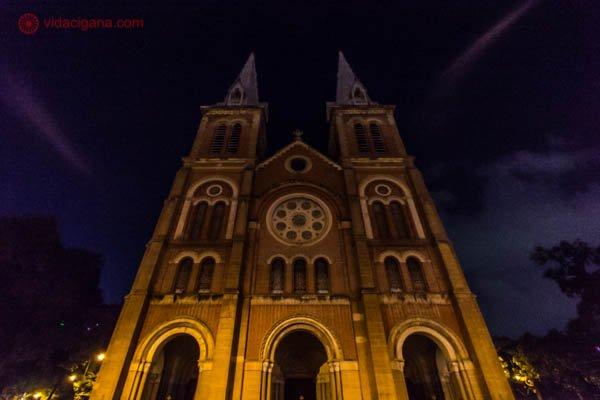 Catedral de Notre Dame, na Cidade de Ho Chi Minh, no Vietnã. A igreja é de estilo neo-romântico, com duas torres em sua fachada, cujas pontas são pontiagudas. Possui uma rosetta em seu meio. A igreja está parcialmente iluminada com uma luz amarelada e o céu está escuro. A foto foi tirada de baixo pra cima e de noite.