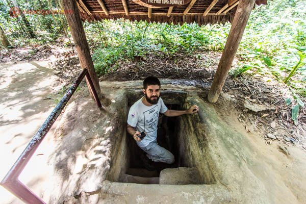 Homem moreno de barba entrando em um túnel subterrânio na região de Cuchi, próximo a Cidade de Ho Chi Minh, no Vietnã. O homem está parado nos degraus do túnel, que é bem pequeno e apertado. O túnel está coberto por uma estrutura de madeira e palha. Essa região foi uma das mais ativas durante a Guerra do Vientã.