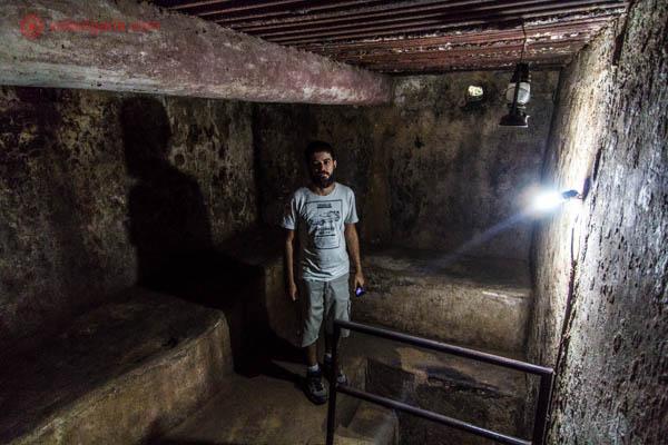 Homem moreno de barba dentro de um túnel na região de Cuchi, próximo da Cidade de Ho Chi Minh, no Vietnã. O túnel é escuro e um pouco amplo.